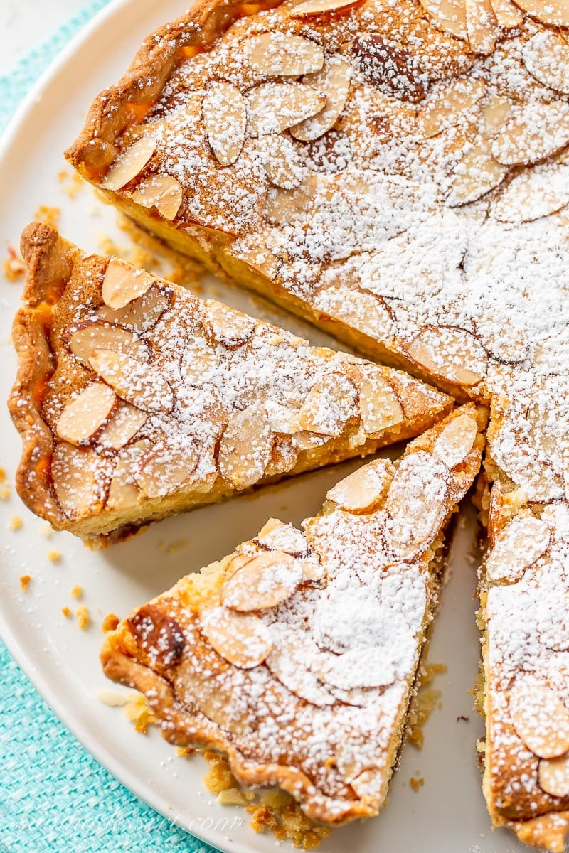 An overhead view of a sliced tart topped with almonds and dusted with powdered sugar