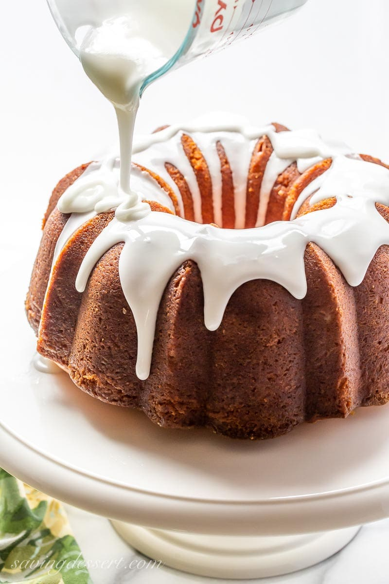 A lemon bundt cake being drizzled with a lemon icing from a measuring cup