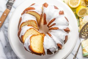 An overhead view of a sliced Lemon Bundt Cake topped with a drizzled icing