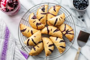 Blueberry Hand Pies in a pile on a cooling rack