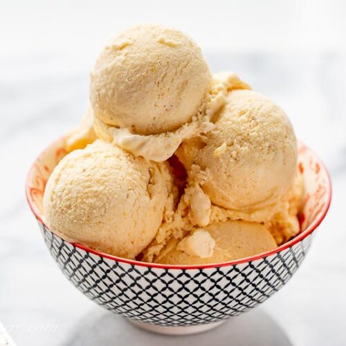 A small bowl with scoops of mango ice cream and a spoon